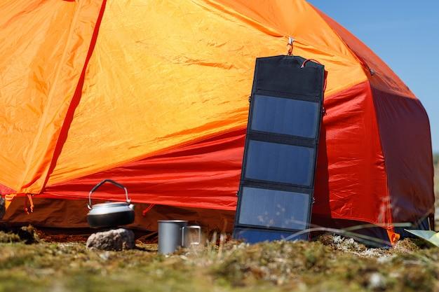 Turystyczny panel słoneczny na pomarańczowym namiocie na zewnątrz. sprzęt kempingowy, alternatywne źródło energii.