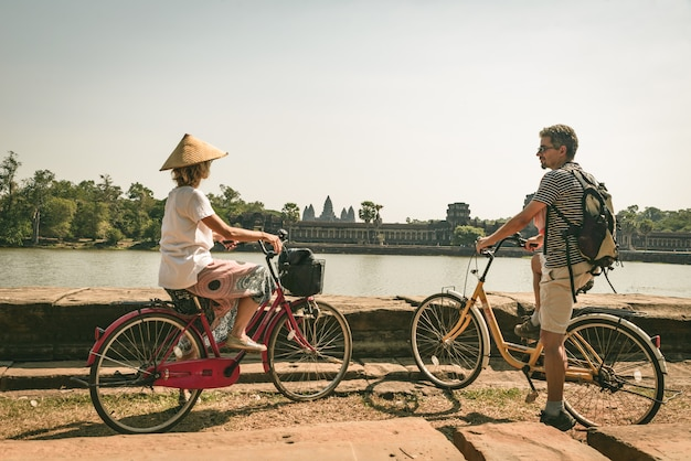 Turystyczny pary kolarstwo w angkor świątyni, kambodża. fasada główna angkor wat odzwierciedlenie w stawie wody. podróżowanie przyjazne środowisku. stonowanych
