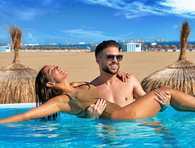 Turystyczny pary skąpanie w nieskończoność basenie na plaży