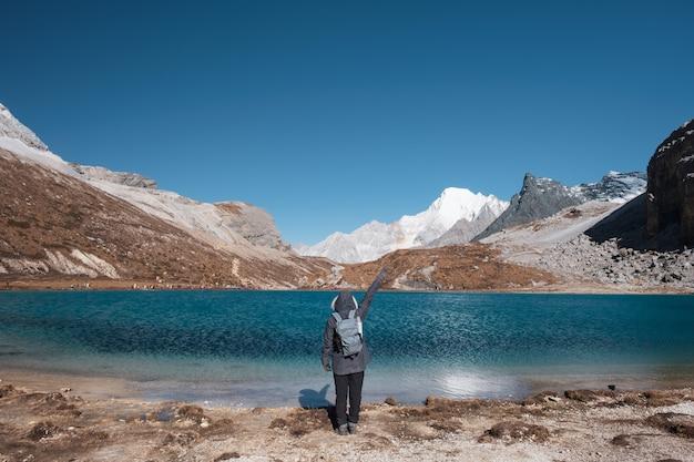 Turystyczny podnieść rękę z turkusowym jeziorem i pasmem górskim na szczycie