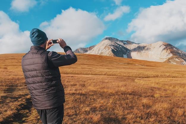 Turystyczny podróżnik fotografuje góry pokryte chmurami na smartfonie