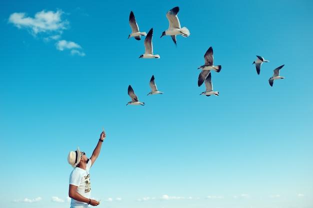 Turystyczny samiec karmiący stado mew na plaży na tle błękitnego nieba clea