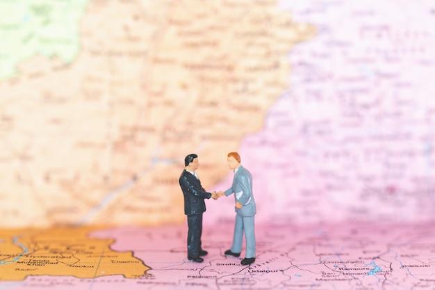 Turystyczny uścisk dłoni na światowej mapy tle