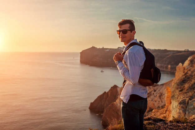 Turystyczny wycieczkowicza odprowadzenie biel plażą na morzu egejskim santorini wyspie grecja cieszy się lato krajobraz. mężczyzna podróżujący
