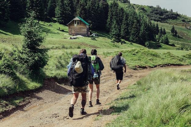 Turystyka, góry, styl życia, natura, koncepcja ludzi - grupa turystów z plecakami idzie szlakiem w kierunku grzbietu górskiego. styl backpackers. koncepcja aktywnego wypoczynku...