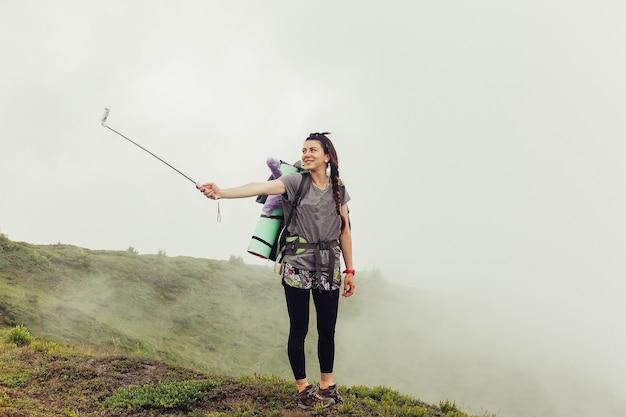 Turystyka, góry, styl życia, przyroda, koncepcja ludzi - dziewczyna w górach alpinizm podróże styl życia koncepcja krajobraz na tle wakacje przygoda podróż plenerowa, robi selfie na telefon