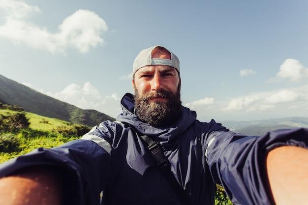 Turystyka, góry, styl życia, przyroda, ludzie, koncepcja selfie - młody człowiek podróżnik sprawia, że selfie na tle gór w lecie, o zachodzie słońca. uśmiechnięty turysta brodaty