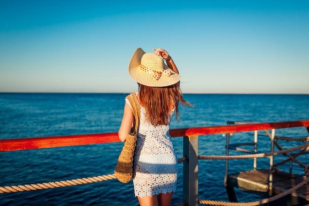 Turystyka. młoda kobieta podróżnik podziwiając krajobraz na molo nad morzem czerwonym. moda letnia