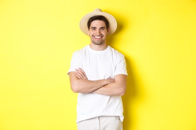 Turystyka. przystojny młody mężczyzna wygląda szczęśliwy, ubrany w słomkowy kapelusz do podróży, skrzyżowane ręce na piersi i uśmiechnięty, stojąc na żółtym tle.