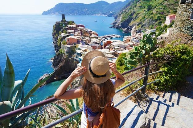 Turystyka w cinque terre we włoszech. młoda kobieta z plecakiem spaceruje po lazurowym szlaku i patrzy na wioskę vernazza we włoszech.