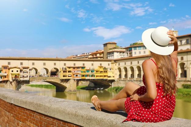 Turystyka w toskanii. widok z tyłu młodej kobiety mody siedzi i patrząc na most ponte vecchio we florencji, włochy.