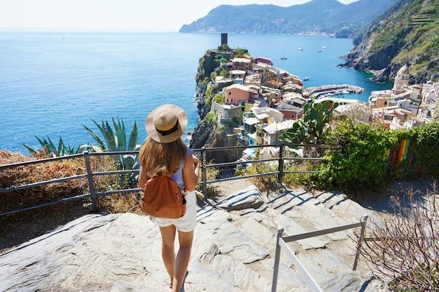 Turystyka we włoszech. młoda kobieta backpacker schodząc na dół w parku narodowym cinque terre. piękna dziewczyna idzie lazurowym szlakiem i patrząc na miasto vernazza, włochy.