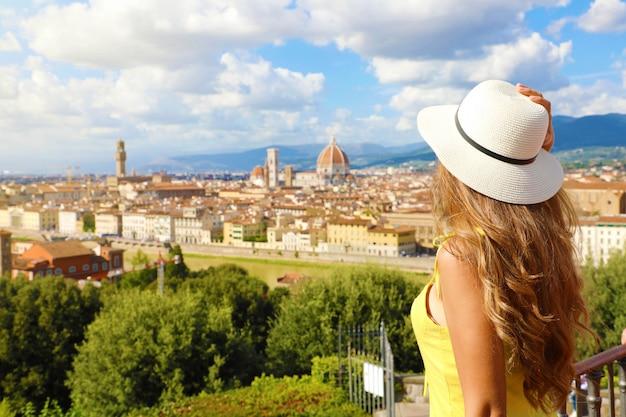 Turystyka we włoszech. widok młodej kobiety z tyłu, ciesząc się panoramicznym widokiem na miasto florencja, toskania, włochy.
