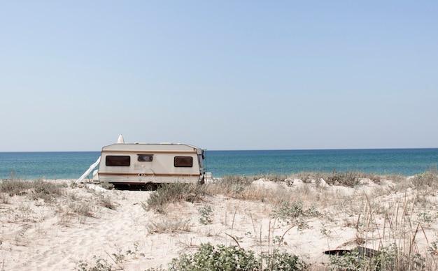 Turystyka, wypoczynek i podróże. turystyczna furgonetka i piaszczysta plaża z widokiem na wybrzeże morza czarnego na południu ukrainy, w regionie chersoniu. europa