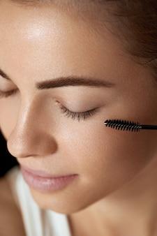 Tusz do rzęs. kobieta, stosując czarny tusz do rzęs na rzęsy za pomocą pędzla do makijażu. piękna młoda kobieta twarz z naturalnych brwi i rzęs.