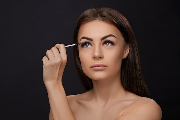 Tusz do rzęs, makijaż upiększający, świeża miękka skóra i długie czarne grube rzęsy nakładające tusz do rzęs za pomocą pędzla kosmetycznego, przedłużanie rzęs, sztuczne rzęsy,