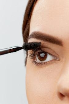 Tusz do rzęs. zbliżenie twarzy pięknej młodej kobiety z makijaż uroda, świeżej skóry miękkiej i długie czarne grube rzęsy, stosując tusz do rzęs z pędzelkiem kosmetycznym.