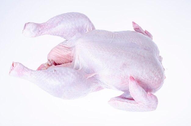 Tusza surowego kurczaka ze skórą na białym tle.
