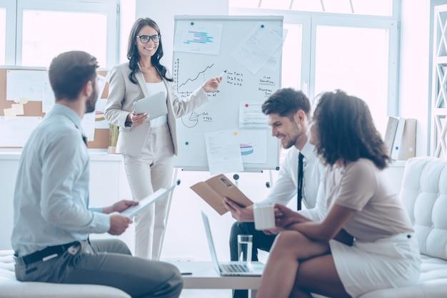 Tutaj widzimy wzrost! młoda piękna, wesoła kobieta wskazująca na tablicę i rozmawiająca o czymś ze swoimi współpracownikami z uśmiechem stojąc w biurze