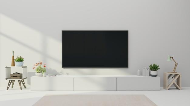Tv na gabinecie w nowożytnym żywym pokoju z rośliną na biel ściany tle.