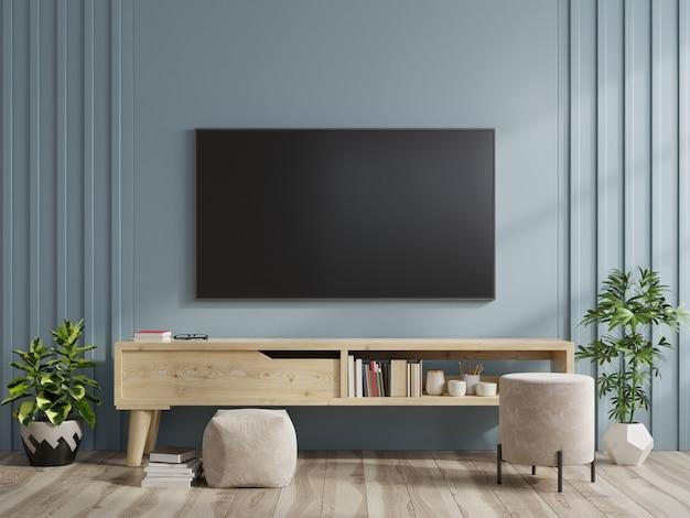 Tv na szafce w nowoczesnym salonie na granatowym tle ściany.