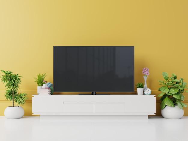 Tv na szafce w nowoczesnym salonie z lampą, stołem, kwiatem i rośliną na żółtym tle ściany