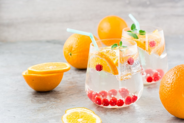 Twardy koktajl seltzer z pomarańczą, żurawiną i miętą w szklankach i pokrojone pomarańcze na stole