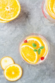 Twardy koktajl seltzer z pomarańczą, żurawiną i miętą w szklankach na stole