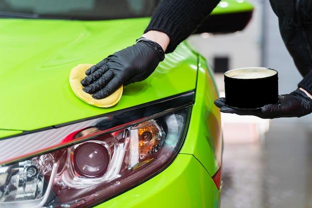 Twardy wosk do ochrony lakieru samochodowego za pomocą gąbki do usuwania zarysowań lakieru. nakładanie twardego wosku żółtą gąbką. ochrona lakieru.
