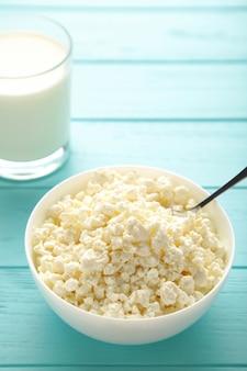 Twaróg i mleko na śniadanie w misce na niebieskim tle. zdjęcie pionowe