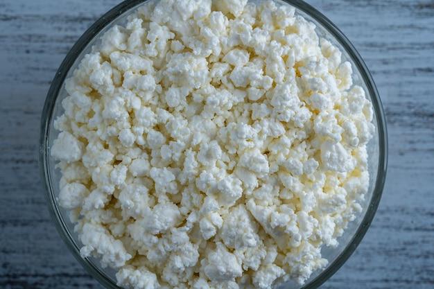 Twaróg w szklanej misce tła, widok z góry. białe ziarniste tekstury produktów mlecznych, twarożek z bliska. koncepcja produktów mlecznych