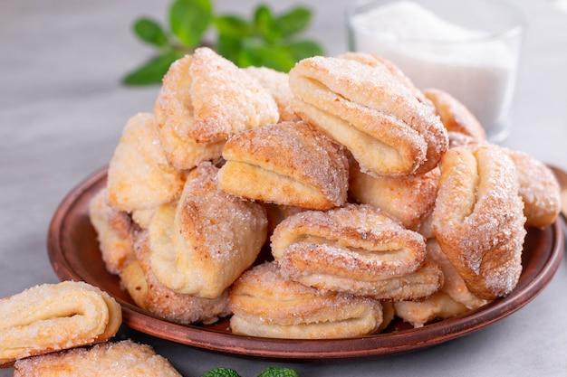 Twarożek ciasteczka z twarogiem i cukrem na talerzu na jasnym tle i ciasteczka cukrowe kurze łapki, wielkanoc przepis