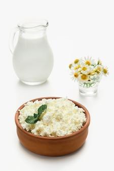 Twarożek granulowany w fajansie obok dzbanka mleka. zbliżenie, selektywne focus, jasne białe tło. twarożek miękki, naturalna zdrowa żywność, pełnoporcjowa karma dietetyczna