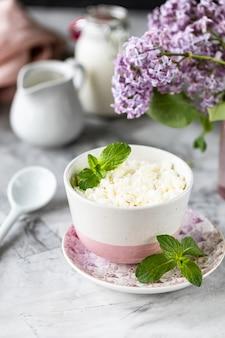 Twarożek śniadaniowy z jagodami, śmietaną, mlekiem na białym stole i gałęzią kwiatów.