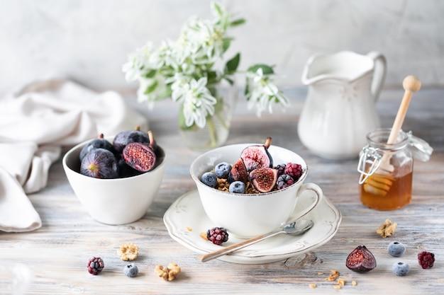 Twarożek z figami, jagodami, miodem i filiżanką kawy z dzbankiem do kawy