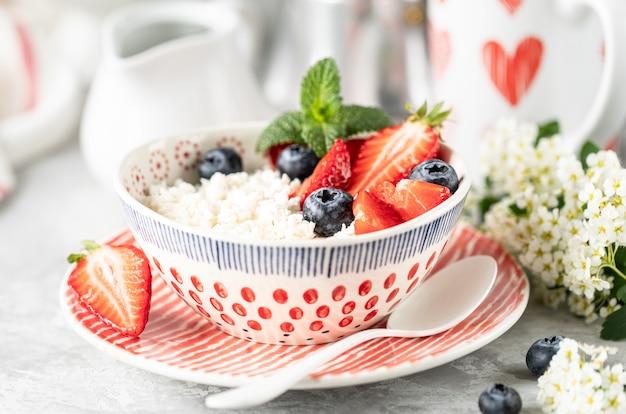 Twarożek z jagodami, dżemem, świeżymi truskawkami i filiżanką kawy ze śmietaną na śniadanie.
