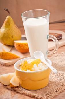 Twarożek z konfiturą gruszkową w misce i szklanką mleka