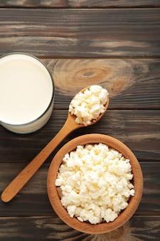 Twarożek z mlekiem na śniadanie w drewnianej misce na brązowym tle. zdjęcie pionowe