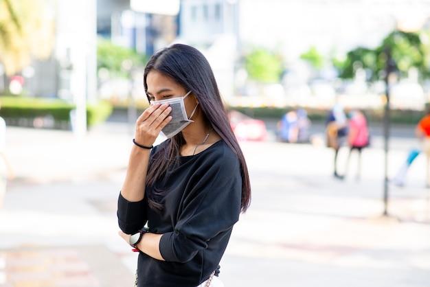 Twarz azjatyckiej kobiety noszącej maskę do ochrony przed wirusami lub zanieczyszczeniami z zewnątrz w tle miasta.