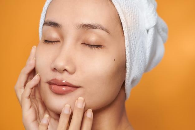 Twarz azjatyckiej kobiety, uśmiechając się i dotykając jej twarzy, nosić ręcznik. koncepcja pielęgnacji skóry i kosmetologii, na pomarańczowym tle