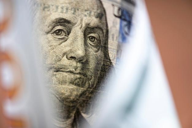 Twarz benjamina franklina na banknocie dolara amerykańskiego. dolar amerykański jest główną i popularną walutą wymiany na świecie. koncepcja inwestycji i oszczędności.