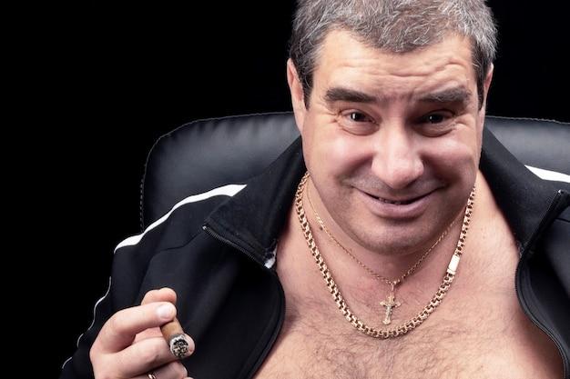 Twarz białego, grubego dorosłego mężczyzny w zbliżeniu. uśmiech rosyjskiego autorytetu kryminalnego lub bandyty palącego cygarowy portret