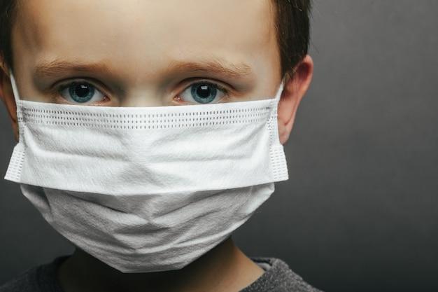 Twarz chłopca noszącego maskę ze strachem w oku close-up na szarej powierzchni. koncepcja koronawirusa i zanieczyszczenia powietrza pm2,5