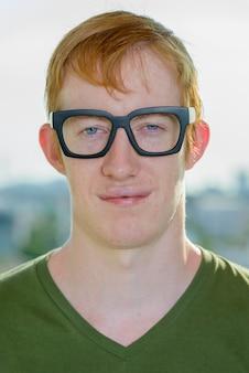 Twarz człowieka nerd z rudymi włosami w okularach z widokiem na miasto