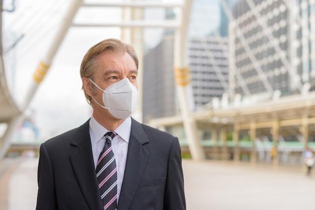 Twarz dojrzałego biznesmena noszenia maski i myślenia o skywalk bridge