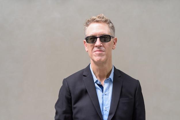 Twarz dojrzałego biznesmena w garniturze myśli z okularami przeciwsłonecznymi na zewnątrz