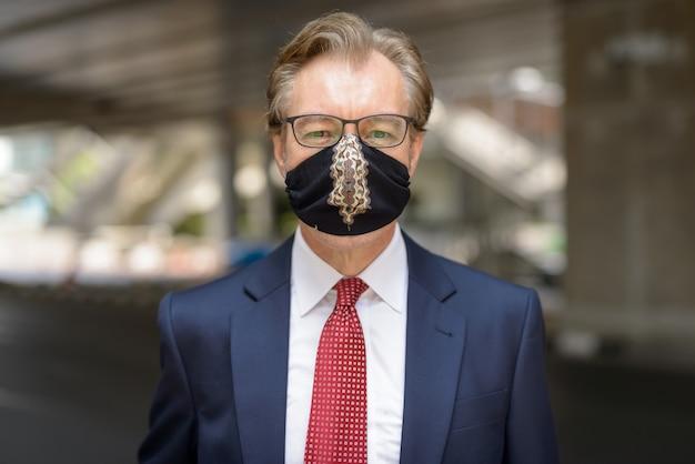 Twarz dojrzałego biznesmena w masce w celu ochrony przed wybuchem wirusa koronowego na ulicach miasta