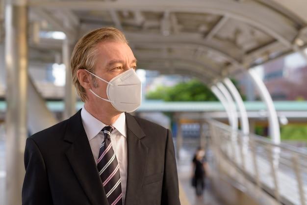 Twarz dojrzałego biznesmena z maską do ochrony przed epidemią koronawirusa myśląca przy kładce