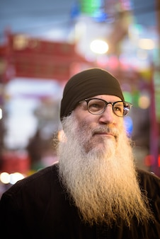 Twarz dojrzały, brodaty turysta mężczyzna myśli w okularach w chinatown