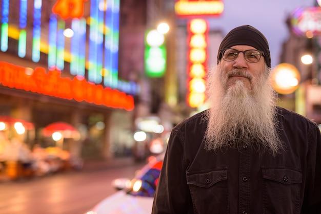 Twarz dojrzały, brodaty turysta mężczyzna w okularach myśli w nocy w chinatown